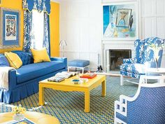 A wall covered in sunshine yellow suede forms a bold backdrop for the living room's royal blue upholstery scheme. A yellow lacquered coffee table and yellow trim on the curtains' cornice add even more punch to the mix. (Photo: Jeremy Samuelson)