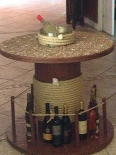 Liquor Cable spool Table with Ice bucket in the middle decorated with tiny ocean stones and mother of pearl shells.