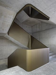 Concrete and brass staircase with a Brutalist feel. Visit houseandleisure.co.za for more