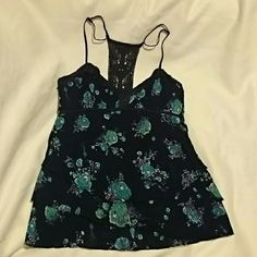 SALE! *HP!* FREE PEOPLE Navy Floral Tank SALE! Free People Navy Floral Tank with teal flowers. Crocheted T-Back. Material at top chest area is intentionally frayed, as seen in 4th pic. Adjustable spaghetti straps. Material is layered/tiered at the bottom...has 3 tiers. Invisible side zipper. EXCELLENT CONDITION!  10% discount when you purchase 2+ listings!!! Free People Tops Tank Tops