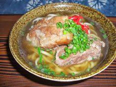 フクギ並木の中央あたりにあるレストラン岬のおすすめは、大きな肉がのったソーキそば。沖縄風スペアリブの骨付きソーキと、骨まで食べられる軟骨ソーキの両方がそばの上に乗っている。スープは