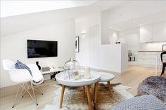 cuisine ouverte sur le salon moderne, aménagé avec deux tables basses en blanc et bois, une chaise Eames blanche, un tapis en peau de vache et écran TV plat