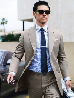 Den Look kaufen: https://lookastic.de/herrenmode/wie-kombinieren/anzug-hellbeige-businesshemd-weisses-und-blaues-krawatte-dunkelblaue/14461   — Schwarze Sonnenbrille  — Weißes und blaues vertikal gestreiftes Businesshemd  — Dunkelblaue Strick Krawatte  — Hellbeige Anzug