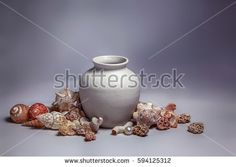 Seashells, sea stones with holes and pearl around the pot