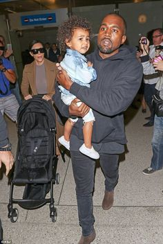 Doting dad: Kanye carried North as he and Kim arrived at LAX on April 16...