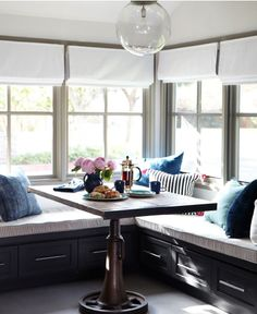 kitchen nook in modern rustic farmhouse // roman shades, blue throw pillows, pendant