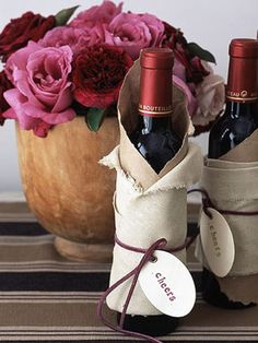 Triangle of craft paper around bottle, followed by fabric and leather tie with tag. #gift