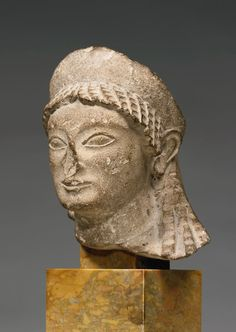 Cypriot limestone head of a Kore, circa late 6th Century B.C. Wearing a chiton, concave disk earrings, and high crested stephane, her deeply grooved hair radiating from the crown, parted above the forehead, and falling in a long unworked mass over the back, three wavy tresses escaping onto her left shoulder, 15.3 cm high. Private collection