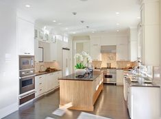 This kitchen sandwiches light natural wood texture between layers of white cabinetry, with large matching island over dark natural wood flooring.