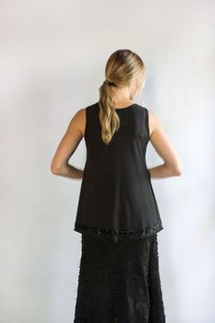 "Our Beaded A-Line Tunic is hand stitched using our 100% organic cotton lightweight jersey. It has a 3/4"" band of armor beading placed 1"" from the bottom edge of the top. The top is fitted through the bust with an empire-style flare that lands just below the hip, providing a comfortable, yet feminine shape. Measures 31 1/2"" from shoulder. Choose your size and color below. Please allow three to six weeks for delivery. Wash gently + Hang to dry. Made in the USA."