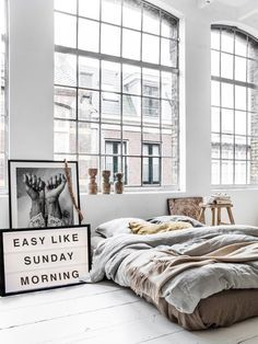 """A gorgeous and cozy neutral bedroom with """"Easy Like Sunday Morning"""" sign and black and white framed photograph"""