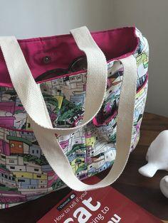 Bolsa em tecido estampado com forro em gorgurão, bolsos externo e interno. <br> Obs.: Objetos não incluídos.