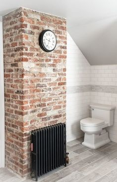 Amazing bathroom features clock on exposed brick wall as well as subway tile backsplash accented with gray mosaic tiles over wood like tiled floor.