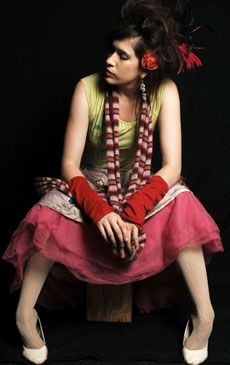 Imogen Heap.  Musician. Photo taken by Brian Appio (MTV) Lime green/yellow tank, sleeveless top, red feathers and flowers in her hair, long earrings.  Striped scarf.  Layerd pink skirt, white shoes.