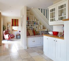 when the kitchen opens onto several rooms, create a balanced flow with a cohesive color palette: splashes of red tie together the kitchen counter accents, the nook bench cushion and the living room chair and window treatment
