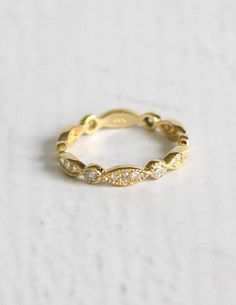 The Victoria Gold is a stunning 1930s style, reproduction antique diamond pave wedding ring. With 0.4 carats of diamonds in a pave setting, the design wraps partially around the band in beautiful elegance. All the diamonds are white color with SI clarity. The ring is made up of 14 carat yellow gold and its overall weight is 2 grams. A sweet edition to any vintage nuptials!  Retail Price: $1,500.00  OUR PRICE: $600.00 (total savings of $900.00)  *NOTE: Diamond engagement ring in photos is not…