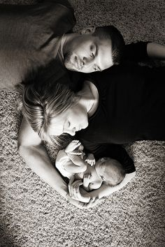 great newborn pic of mom and dad cradling baby.