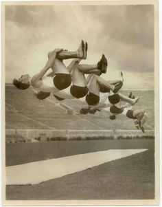 "Handwritten caption: ""Los Angeles A.C. tumblers in a flip-flop, nine of them, while practicing in Pasadena Rose Bowl for Olympic gymnastics team."" Feb-1932"