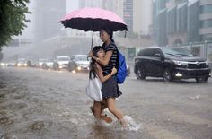 A girl clings to her mother as they travel on a flooded street amid heavy rainfall in Shenzhen, Guangdong province, China, July 24, 2015. Approximately a million people have been affected by severe downpours in several Chinese provinces, causing collapsed houses, decimating crops as well as blocking highways, reported Xinhua News Agency. REUTERS/Stringer
