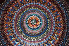 Bottle caps arranged on the floor to form mandalas..http://www.tomdeiningerart.com/works.html