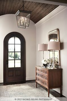 The entrance foyer with arched ceiling mirrors the shape of the door and incorporates a wood ceiling with a rustic lantern adding just the right amount of character. Simple, classic furnishings with just a touch of shimmer complement the rich wood hue. Entrance Foyer, House Entrance, Custom Home Builders, Custom Homes, Paris Home, Wooden Ceilings, Design Blog, Design Design, Classic House