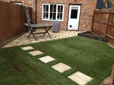 Small garden patio incorporating stepping stone path, freshly laid turf and some new lap panels.