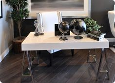 love this lacquer white desk with chrome sawhorse legs. the diagonal charcoal wood floors. oh and the white chair with black piping.