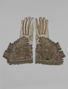 Gloves (Pair of) Date: first half 17th century Culture: English Medium: Leather; canvas worked with silk and metal thread; tent, Gobelin, detached buttonhole variations, and plaited braid stitches; metal bobbin lace; silk and metal ribbon Dimensions: L. 13 1/4 x W. 8 inches (33.7 x 20.3 cm) Classification: Textiles-Embroidered