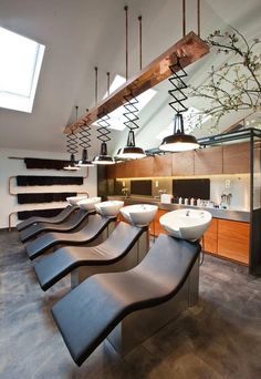 Dutch designer Dirk van Berkel converted a fireplace shop in Amsterdam into a salon and hairdressing school with copper pipes snaking across the walls and ceiling.