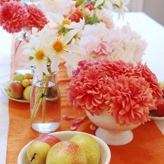The low coral dahlia arrangement in the white vase would make a great centerpiece at Brittany's reception.