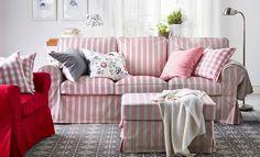 Soggiorno con divano bianco, poltrona con plaid e cuscini beige e marrone chiaro e tappeto con motivo marrone e bianco.