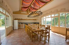 Spacious kitchen diner with hanging rack style light fitting and fabric ceiling decoration in Maison Osse, French holiday rental property which sleeps 12. www.purefrance.com