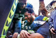 Seahawks quarterback Russell Wilson is comforted by teammate O'Brien Schofield following the Seahawks victory over the Green Bay Packers during the NFL Division Championship game at CenturyLink Field in Seattle on Sunday, Jan. 18, 2015. (Photo by Tony Overman/The Olympian)