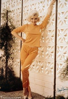 Late photographer George Barris captured the Los Angeles-born star posing against a white wall in an orange top and trousers