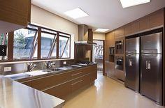 Cozinha com móveis escuros. Armário embutido e tampo de inox da Mekal, projeto de Denise Meirelles, com duas geladeiras e iluminação embutida.