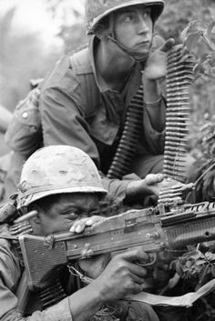 Machinegun team huddles behind bushes in a hedgerow and returns the fire of North Vietnamese Army regulars in trenches and foxholes in Vietnam on March 13, 1967. Troops of the U.S. 1st Air Cavalry Division battled for more than ten hours after two companies were caught in heavy crossfire of communist rifle and automatic weapons fire. (AP Photo/Hodierne)