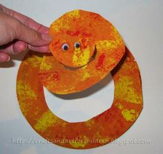 Give the children a sponge dipped half in red and half in yellow to dab all over creating snake skin. Make sure to dab off any excess paint on a different piece of paper 1st before pressing it down of the snake craft.  Let dry, draw the circular snake pattern - cut along drawn line.