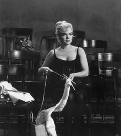 Marilyn Monroe sits in a leotard and corset combination while knitting, in a still from director George Cukor's film, 'Let's Make Love'.