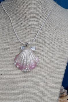 Beautiful Mermaid pendant . Real sea shell , airbrushed in soft pink and pearl. Faux pearls and iridescent tiny glass balls added for a unique look.  Resin coated for increased strength. At widest measures 48mm.  Comes with pearl leather cord.  No two are alike making each a one-of-a-kind.   (S1)