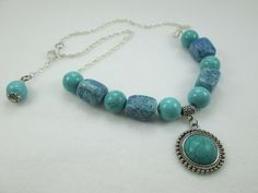 AN EXCITING, CHUNKY, TURQUOISE NECKLACE WITH A HOOK AND EYE CLOSURE.  A ROUND GLASS TURQUOISE BEAD THAT MATCHES THE OTHER ROUND BEADS DANGLES AT THE END OF THE NECKLACE.  T...