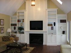 Fireplace with TV above; white wood media shelving and cabinets on the sides