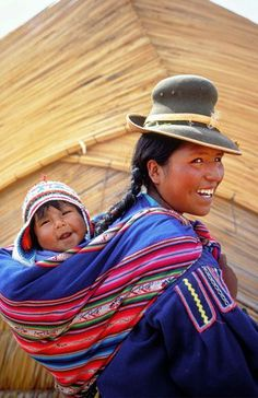 A young female carrying her baby at the body back Peru