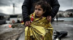CNN _ EUROPE ON REFUGEES - A father stands with his daughter as refugees and migrants arrive on the Greek island of Lesbos after crossing the Aegean Sea.