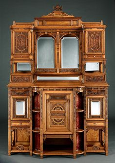 The maker has chosen to use a richly grained satinwood, and executed the carving with extraordinary fluency and precision, foliates, putti and birds are featured; over the open sectioned base, quadrant shelves flank the lower door; above, double bevelled and arched mirrors have flanking cupboards with richly carved fascias, conjoined by a running gallery, and, surmounted by a serpentine shaped cornice. Circa 1885