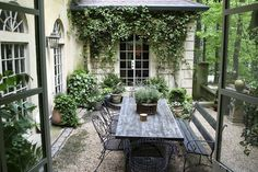 Serene setting. Lots of green in large pots, old table and mis-matched seating.  The use of gravel really keeps the expense down. Although the house is the real secret of this garden, the patio design itself would be fairly easy to duplicate.