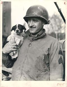 1944- U.S. soldier holds Oscar, mascot of a signal company of the 4th Armored Division, in Fenetrange, France.