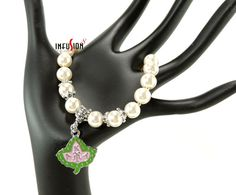 Set of 2 Bracelets Alpha Kappa Alpha AKA Emblem & Ivy Charms  Hand Made  Unique  Classy  Stylish  ♦♦Bracelet 1♦♦ This beautiful bracelet is made with Pearl glass beads, Silver Bali style pewter beads, Pink colored Swarovski crystal beads And highlighted with a special & unique glass bead that has pink roses enveloped inside a light green bead  This bracelet comes with an extender chain to CUSTOM FIT most wrist Size 7 inches - 8 inches   ♦♦Bracelet 2♦♦ This beautiful charm bracelet ...
