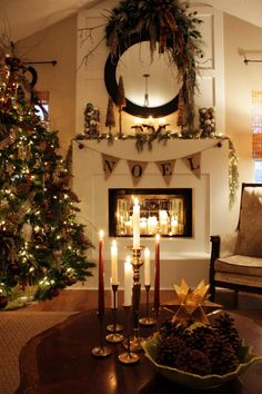 Burlap Pennant Banner.  Ornaments in clear cylinder vases.  Lighted garland.  Lit candles in fireplace. Candle arrangement on table.