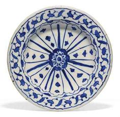 AN IZNIK BLUE AND WHITE POTTERY TAZZA OTTOMAN TURKEY, CIRCA 1560 Of typical form, rising from conical foot to rounded body with wide everted rim, the white ground painted in cobalt-blue with central rosette surrounded by radial pattern with cusped arch finials, the rim with scrolling flowers between two cusped lines, exterior with similar cusped lines along underside of rim and around foot, exterior with alternating palmettes and circles, intact 7 5/8in. (19.3cm.) diam.