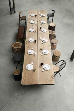 Langer Holztisch mit Holzstämmen als Hocker und verschiedenen Stühlen